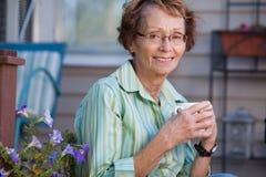 Femme aîné avec la boisson chaude à l'extérieur Images libres de droits