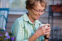 Femme aîné avec la boisson chaude à l'extérieur Image stock