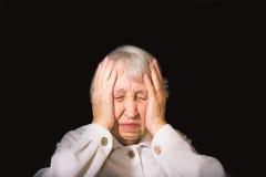 Femme aîné avec la tête dans des mains semblant lasses Photographie stock libre de droits