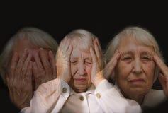 Femme aîné avec la tête dans des mains semblant lasses Image stock