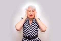 Femme aîné avec la tête dans des mains semblant lasses Photo stock