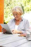 Femme aîné avec la tablette de Digitals Photographie stock libre de droits