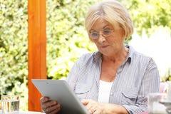 Femme aîné avec la tablette de Digitals Photo stock