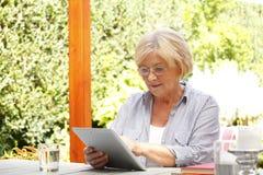 Femme aîné avec la tablette de Digitals Images stock