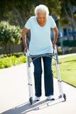 Femme aîné avec la trame de marche Photographie stock libre de droits