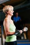 Femme aîné avec le barbell en gymnastique Photographie stock libre de droits