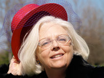 Femme aîné avec le chapeau rouge Photographie stock libre de droits