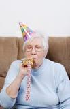 Femme aîné avec le générateur de soufflement de bruit de chapeau d'anniversaire Image libre de droits