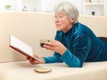 Femme aîné avec le livre et le café Photographie stock
