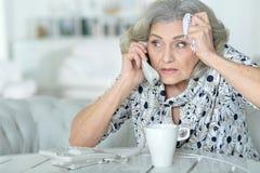 Femme aîné avec le mal de tête Photos stock