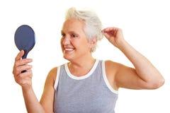 Femme aîné avec le miroir de main Image stock