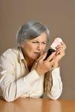 Femme aîné avec le téléphone portable Images stock
