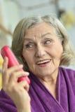 Femme aîné avec le téléphone portable Photos stock