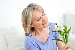 Femme aîné avec les lis blancs Photos stock