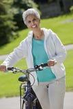 Femme aîné avec sa bicyclette image libre de droits