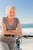 Femme aîné avec son vélo Image libre de droits
