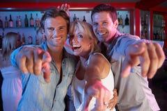 Femme aîné ayant l'amusement dans le bar avec deux jeunes hommes Photo libre de droits