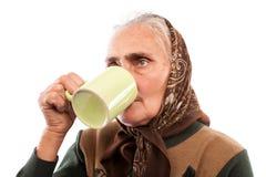 Femme aîné buvant d'une cuvette Photo stock