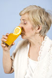 Femme aîné buvant du jus d'orange frais Photo stock