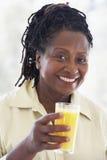 Femme aîné buvant du jus d'orange frais Image stock