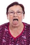 Femme aîné collant à l'extérieur la langue Photographie stock libre de droits