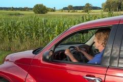 Femme aîné conduisant sur la route rurale par Cornfield photos libres de droits