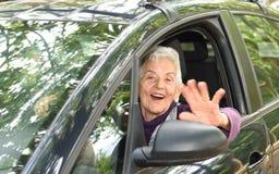 Femme aîné conduisant un véhicule Image stock