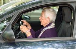Femme aîné conduisant un véhicule Photo stock