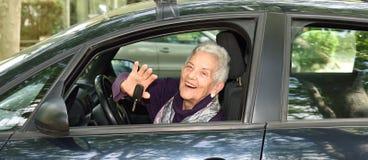 Femme aîné conduisant un véhicule Images stock
