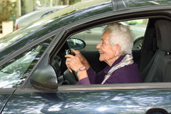 Femme aîné conduisant un véhicule Photos stock