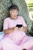 Femme aîné confondu par Texting Images libres de droits
