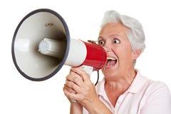 Femme aîné criant dans le mégaphone Photo libre de droits