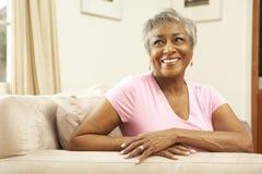 Femme aîné détendant dans la présidence à la maison Photo libre de droits