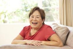 Femme aîné détendant dans la présidence à la maison Photos libres de droits