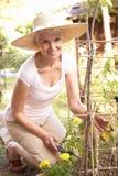 Femme aîné détendant dans le jardin Photos libres de droits