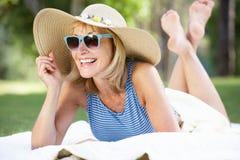 Femme aîné détendant en jardin d'été Photographie stock