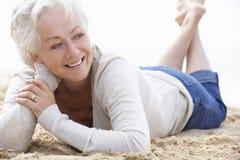 Femme aîné détendant sur la plage Image stock