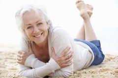 Femme aîné détendant sur la plage Photographie stock