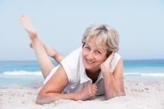 Femme aîné détendant sur la plage sablonneuse Photo stock