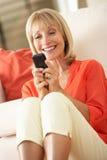 Femme aîné détendant sur le sofa envoyant le message avec texte photographie stock libre de droits