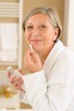 Femme aîné dans la salle de bains regardant l'appareil-photo images stock