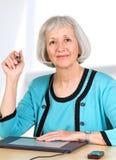 Femme aîné de sourire avec la tablette graphique Image libre de droits
