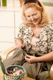 Femme aîné de sourire avec le kit de couture Image stock