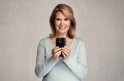Femme aîné de sourire avec Smartphone Images stock