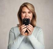 Femme aîné de sourire avec Smartphone Photos libres de droits