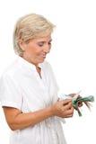 Femme aîné de sourire comptant l'argent Image libre de droits
