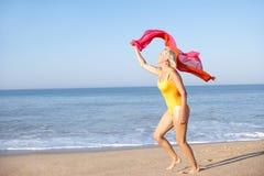 Femme aîné exécutant sur la plage Photos libres de droits