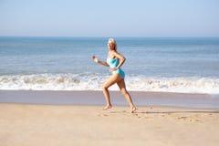 Femme aîné exécutant sur la plage Photos stock