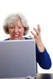 Femme aîné fâché avec l'ordinateur portatif Images stock