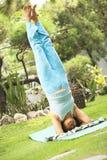 Femme aîné faisant la pratique en matière de yoga Photos stock